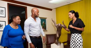 The Minister of Culture, Gender, Entertainment and Sport, the Honourable Olivia Grange (left) and Olympic sprinter, Asafa Powell look on as the sprinter's wife, Alyshia, discusses the details in the maquette of the monument to be erected at the National Stadium in tribute to the runner.